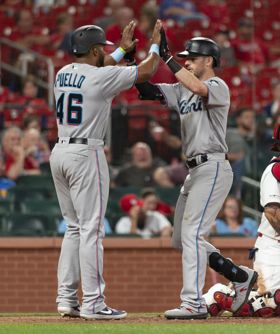 Miami Marlins' JT Riddle, right, celebrates with Cesar Puello, left, after they scored on Riddle's home run during the 11th inning of the team's baseball game against the St. Louis Cardinals, Thursday, June 20, 2019, in St. Louis. (AP Photo/L.G. Patterson)