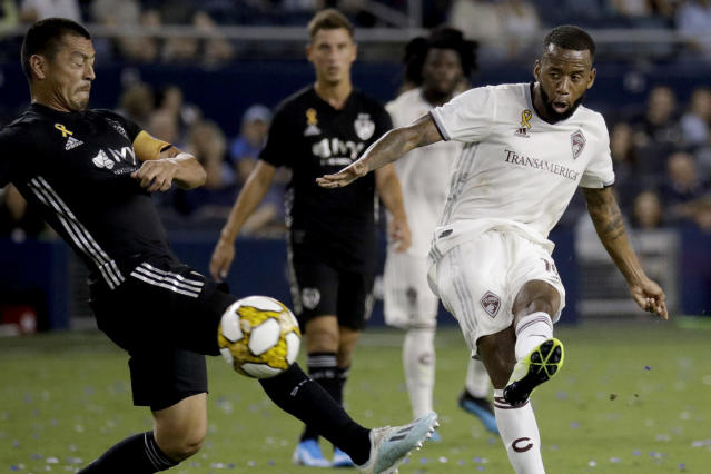 Colorado Rapids midfielder Kellyn Acosta, right, tries to score past Sporting Kansas City midfielder Roger Espinoza during the first half of an MLS soccer match Saturday, Sept. 21, 2019, in Kansas City, Kan. (AP Photo/Charlie Riedel)