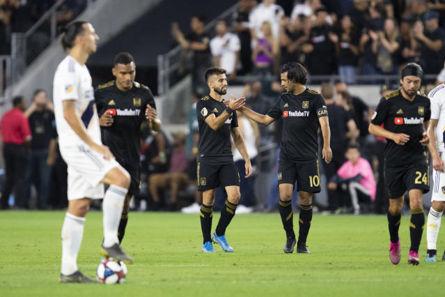 "<a class=""link rapid-noclick-resp"" href=""/soccer/teams/los-angeles-football-club/"" data-ylk=""slk:LAFC"">LAFC</a> celebrates one of the goals from Carlos Vela (10) on Thursday as LA Galaxy forward Zlatan Ibrahimovic looks on. (Kyusung Gong/Getty)"