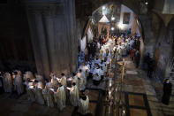 Priests participate in the Easter Sunday Mass led by the Latin Patriarch at the Church of the Holy Sepulchre, where many Christians believe Jesus was crucified, buried and rose from the dead, in the Old City of Jerusalem, Sunday, April 4, 2021. (AP Photo/Oded Balilty)