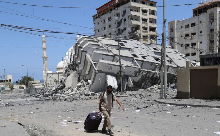 A man pulls his luggage while passing the rubble of a destroyed building which was hit by Israeli airstrikes, in Gaza City, Wednesday, May 12, 2021. (AP Photo/Adel Hana)