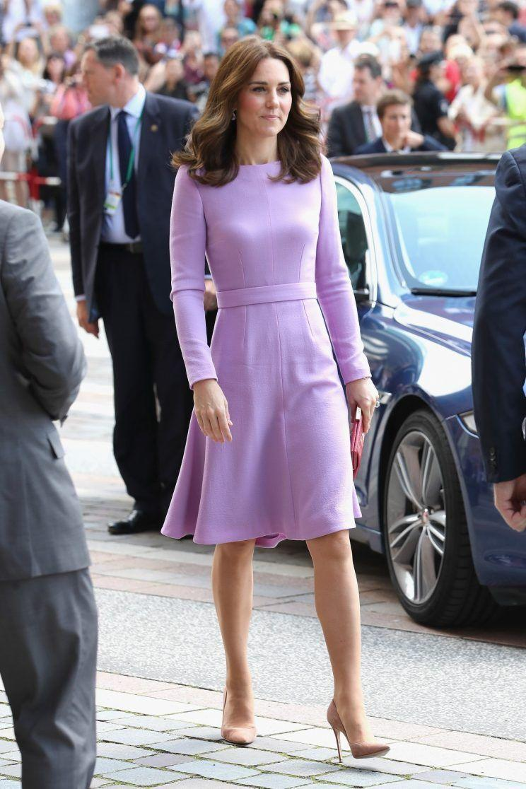 <p>For her final day of engagements in Germany, the Duchess wore a long-sleeved lavender dress by British designer Emilia Wickstead. The custom design contrasted with Kate's red leather clutch.<br><i>[Photo: PA]</i> </p>