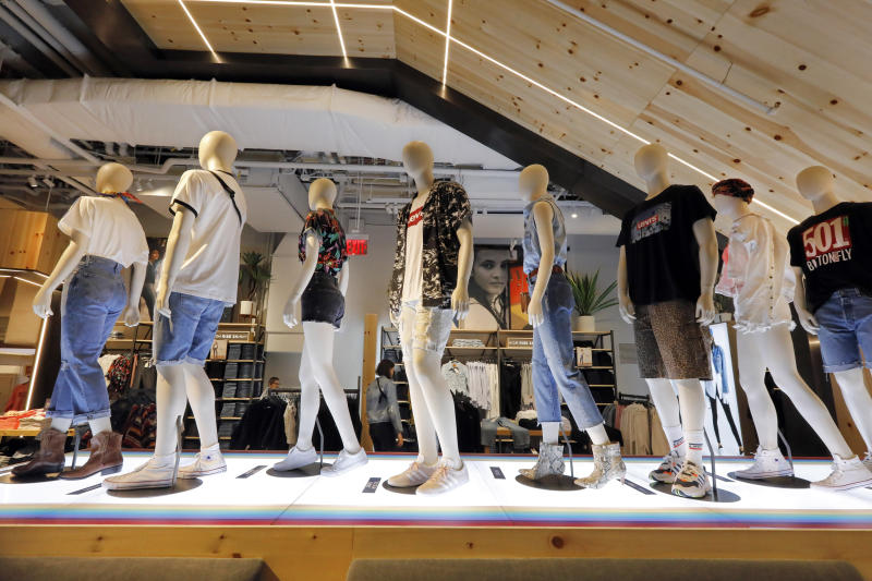 In this June 14, 2019, photo mannequins display Levi's products on the lower level of the Levi's store in the New York's Times Square. Levi Strauss & Co.'s new flagship in Manhattan's Time Square features larger dressing rooms with call buttons and tailors who can add trims and patches to customers' jeans. (AP Photo/Richard Drew)