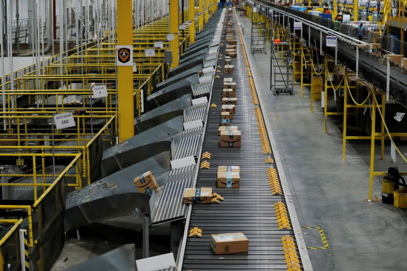 FILE PHOTO: Amazon packages are pushed onto ramps leading to delivery trucks by a robotic system as they travel on conveyor belts inside of an Amazon fulfillment center on Cyber Monday in Robbinsville, New Jersey