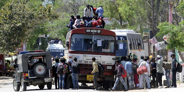 LUCKNOW, INDIA - MARCH 29: Migrant workers try to board an overcrowded bus to return to their home on Day 5 of the 21 day nationwide lockdown imposed by PM Narendra Modi to curb the spread of coronavirus, at Asti Road, Bakshi Ka Talab, on March 29, 2020 in Lucknow, India. (Photo by Dheeraj Dhawan/Hindustan Times via Getty Images)