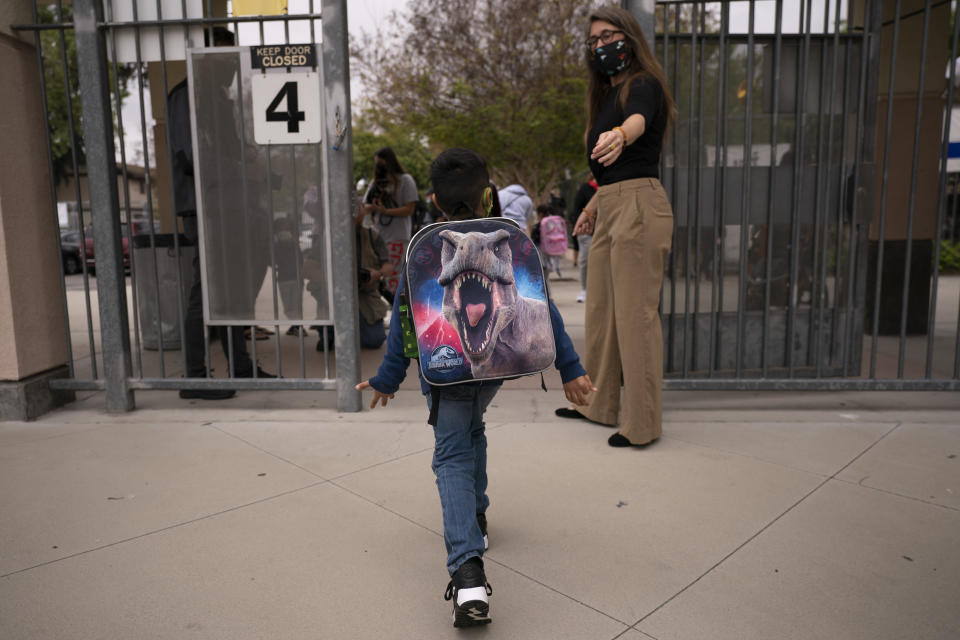 "FILE - Kindergartener Angel Hernandez leaves after the first day of in-person learning at Maurice Sendak Elementary School in Los Angeles, Tuesday, April 13, 2021. A recent spike in coronavirus cases in some states has led one of the nation's top health experts to suggest that governors could ""close things down"" like they did during previous surges. But that doesn't appear likely to happen — not even in states led by Democratic governors who favored greater restrictions in the past. (AP Photo/Jae C. Hong)"