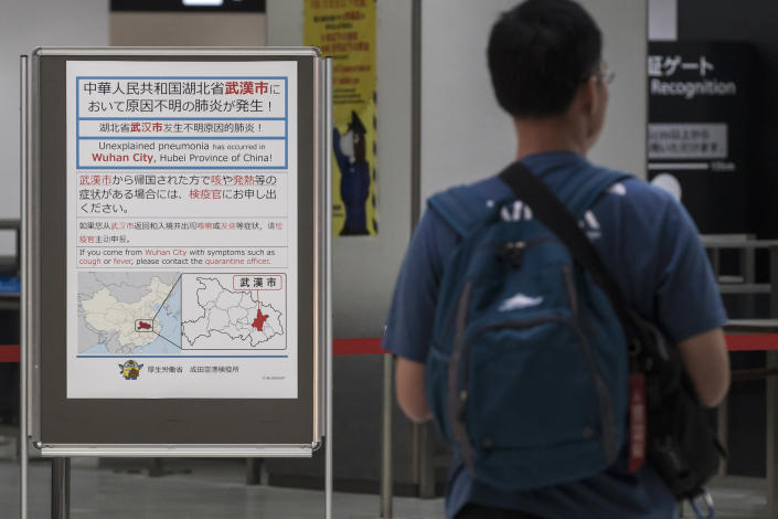 A passenger walks past a notice for passengers from Wuhan, China, displayed near a quarantine station at Narita airport in Japan. (Getty)