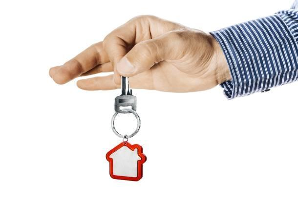 A hand holding out a key for the subletting of a HDB flat