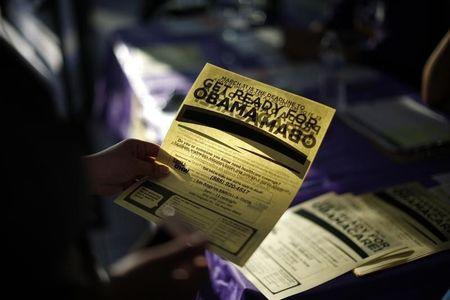 A woman picks up a leaflet at a health insurance enrollment event in Cudahy, California