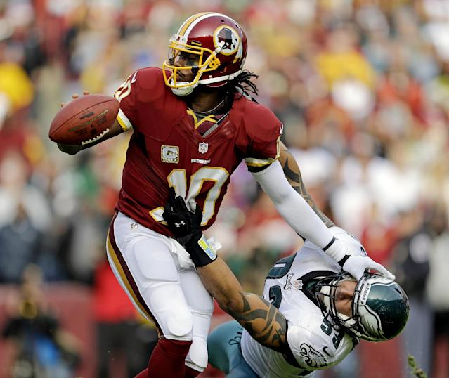Washington Redskins quarterback Robert Griffin III pushes Philadelphia Eagles defensive end Jason Babin away as he looks to get rid of the ball during the first half of an NFL football game in Landover, Md., Sunday, Nov. 18, 2012. (AP Photo/Patrick Semansky)