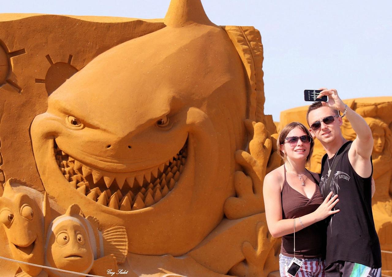"<p>Visitors pose next to a sculpture during the Sand Sculpture Festival ""Disney Sand Magic"" in Ostend, Belgium. (Photo courtesy of Disneyland Paris) </p>"