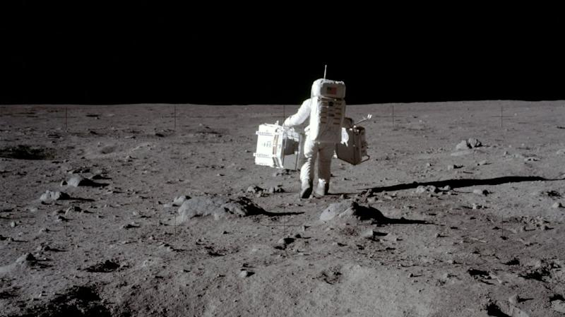 Buzz Aldrin carries equipment for the Passive Seismic Experiments and Laser Ranging Retroreflector at Tranquility Base on the moon