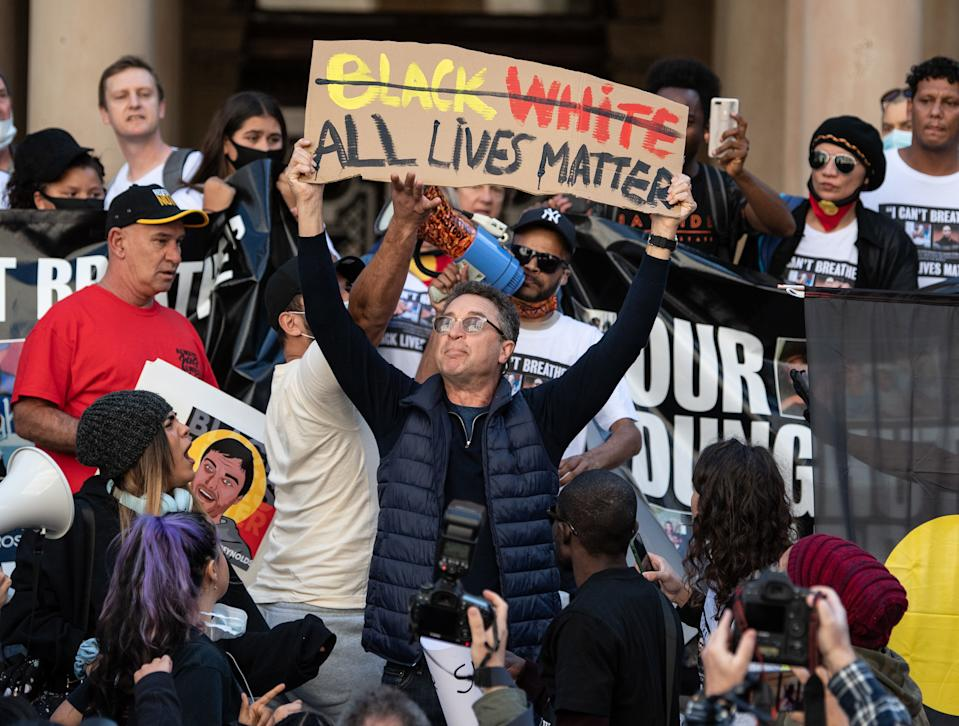 A counter protester holding a sign reading 'All Lives Matter' is confronted in Sydney. Source: AAP