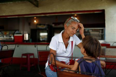 Zulay Pulgar (C), 43, rest in a coffee shop with her son Emmanuel, 4, after standing in line to buy cement in a hardware store in Punto Fijo, Venezuela November 17, 2016. Picture taken November 17, 2016. REUTERS/Carlos Garcia Rawlins