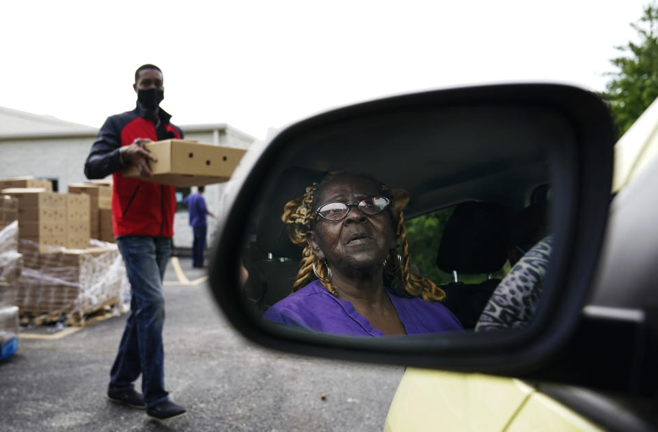 Brenda Fowler, right, of Ferguson, Mo., waits for a package of food from Ken Jenkins, left, at a community food distribution center where a treatment provider is working with pastors in the Black community to bring mobile treatment to the food drive in St. Louis County on Wednesday, May 19, 2021. (AP Photo/Brynn Anderson)