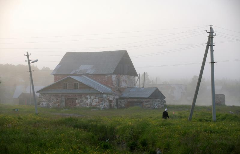 """A woman walks past a house on July 12, 2008 on the Solovetsky Islands, scene of the most notorious Soviet prison camp, later described as the """"mother of the Gulag"""" by dissident author Alexander Solzhenitsyn"""