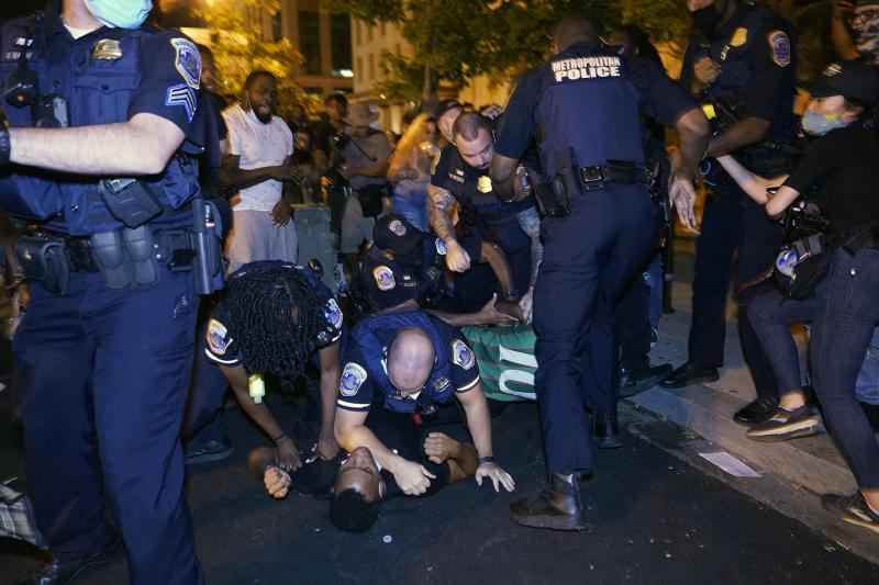 Two police officers pin a Black man down on the ground, surrounded by other police officers and protestors.