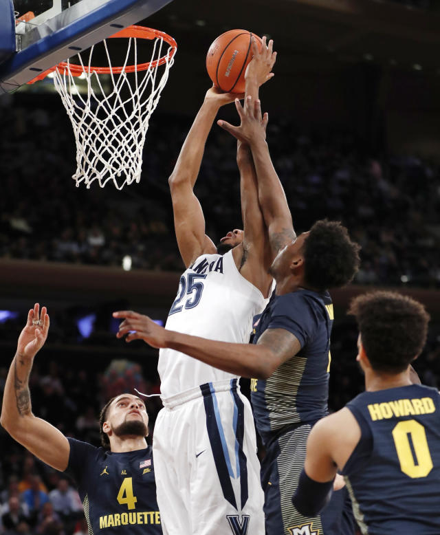 Marquette guard Sacar Anim (2) defends against Villanova guard Mikal Bridges (25) as he goes up for a shot during the first half of an NCAA college basketball game in the quarterfinals of the Big East men's tournament in New York, Thursday, March 8, 2018. Marquette forward Theo John (4) and guard Markus Howard (0) watch. (AP Photo/Kathy Willens)