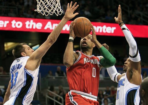 Milwaukee Bucks' Drew Gooden (0) gets between Orlando Magic's Ryan Anderson (33) and Dwight Howard for a shot in the first half of an NBA basketball game, Saturday, March 3, 2012, in Orlando, Fla. (AP Photo/John Raoux)