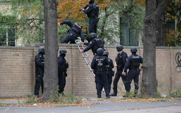 Policemen climb over a wall close to the site of the shooting - DPA