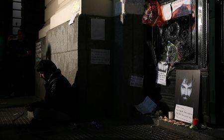A man sits next to a portrait of Santiago Maldonado, a protester who went missing since security forces clashed with indigenous activists in Patagonia on August 1, 2017, at the entrance of a  judicial morgue in Buenos Aires, Argentina October 20, 2017.  REUTERS/Marcos Brindicci