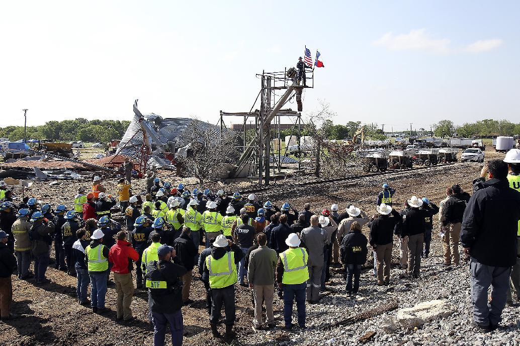 Workers pause for a memorial service at the site of the fire and explosion in West, Texas on Wednesday, April 24, 2013. The explosion at West Fertilizer which killed 14 people left a crater more than 90 feet (27 meters) wide and blasted the walls and windows off dozens of buildings in the town of 2,700. (AP Photo/The San Antonio Express-News, Tom Reel, Pool)