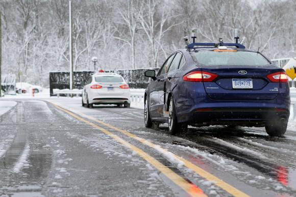 Two Ford Fusions with visible self-driving sensor hardware are shown testing on a snowy road in Michigan.