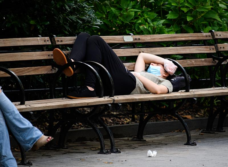 NEW YORK, NEW YORK - AUGUST 08: A person wearing a protective face mask and gloves sleeps in Madison Square Park as the city continues Phase 4 of re-opening following restrictions imposed to slow the spread of coronavirus on August 8, 2020 in New York City. The fourth phase allows outdoor arts and entertainment, sporting events without fans and media production. (Photo by Noam Galai/Getty Images)