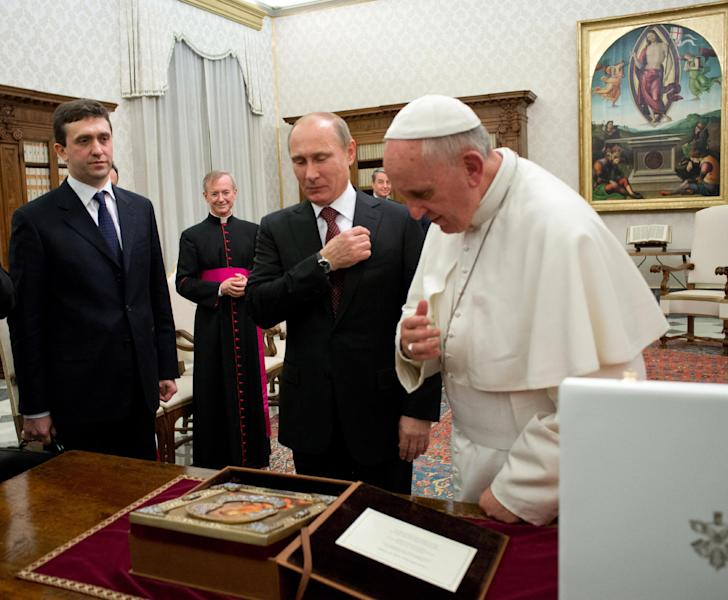 In this photo provided by the Vatican newspaper L'Osservatore Romano, Russian President Vladimir Putin, center, and Pope Francis cross themselves in front of an icon of the Madonna, given to the pontiff by Putin on the occasion of their private audience at the Vatican, Monday, Nov. 25, 2013. Putin presented Francis with an image of the icon of the Madonna of Vladimir, an important religious icon for the Russian Orthodox faithful. After they exchanged the gifts, Putin asked Francis if he liked it, and Francis said he did. Putin then crossed himself and kissed the image, and Francis followed suit. They met privately for 35 minutes Monday evening in the pope's private library. (AP Photo/L'Osservatore Romano, ho)