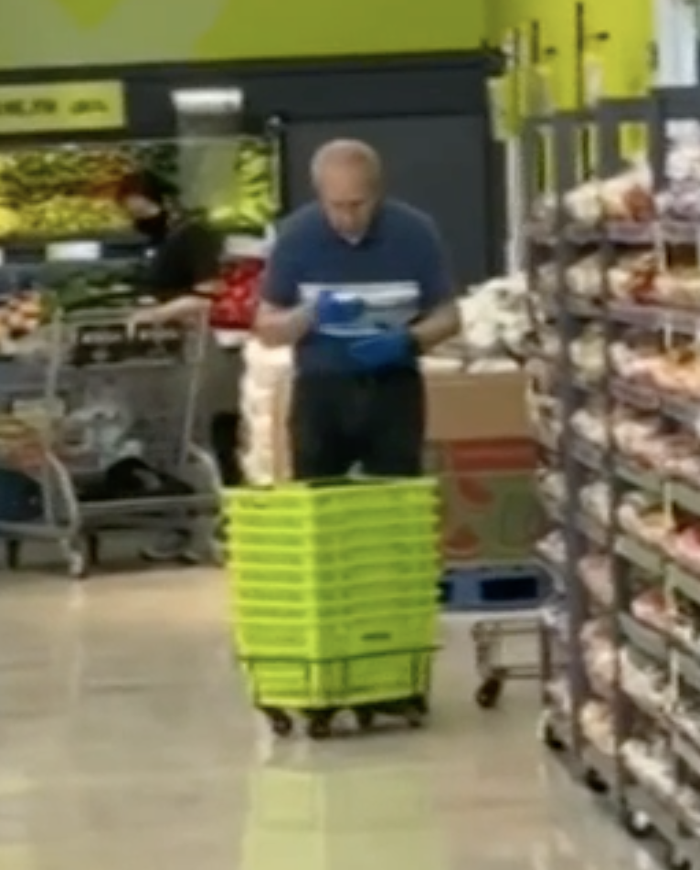 Photo shows a man spitting into a cloth before using it to clean supermarket baskets.
