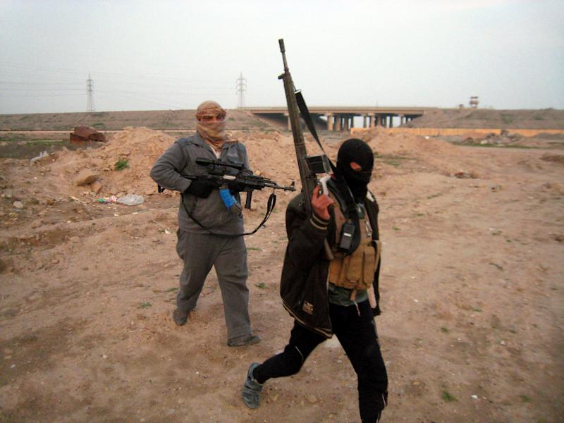 In this Thursday, Jan. 23, 2014 photo, gunmen prepare to take up combat positions in Fallujah, Iraq. Islamic militants controlling a mainly Sunni area west of Baghdad are so well-armed that they could occupy the capital, members of Iraq's al-Qaida branch - known as the Islamic State of Iraq and the Levant - have taken over parts of Ramadi, the capital of the largely Sunni western province of Anbar. (AP Photo)