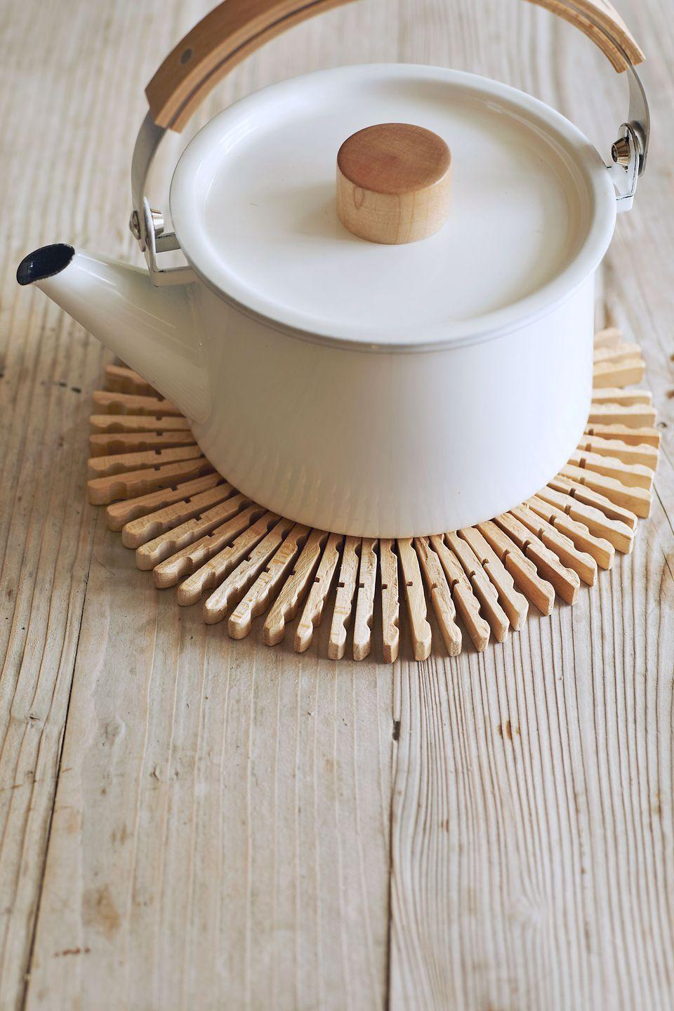 """<p>Whip up a Scandinavian-style table protector from–get this–wooden clothespins and <a href=""""https://www.amazon.com/Paddle-Wire-Gauge-Ounces-Pkg-Bright/dp/B004BQ1HSS?tag=syn-yahoo-20&ascsubtag=%5Bartid%7C10050.g.645%5Bsrc%7Cyahoo-us"""" rel=""""nofollow noopener"""" target=""""_blank"""" data-ylk=""""slk:floral wire"""" class=""""link rapid-noclick-resp"""">floral wire</a>. Oslo-born crafter Paul Lowe shares his easy how-to in <em><a href=""""http://www.amazon.com/Sweet-Paul-Eat-Make-Charming/dp/0544133331?tag=syn-yahoo-20&ascsubtag=%5Bartid%7C10050.g.645%5Bsrc%7Cyahoo-us"""" rel=""""nofollow noopener"""" target=""""_blank"""" data-ylk=""""slk:Sweet Paul Eat and Make"""" class=""""link rapid-noclick-resp"""">Sweet Paul Eat and Make</a></em>. Simply disassemble <a href=""""https://www.amazon.com/Natural-Clothespins-Craft-Boutique-Scrapbooking/dp/B011P8KEQU/?tag=syn-yahoo-20&ascsubtag=%5Bartid%7C10050.g.645%5Bsrc%7Cyahoo-us"""" rel=""""nofollow noopener"""" target=""""_blank"""" data-ylk=""""slk:40 clothespins,"""" class=""""link rapid-noclick-resp"""">40 clothespins,</a> lay them flat side down, and drill a hole in each, about ½ inch from the tapered end. Thread the pins onto the wire with the double-notched sides facing right, as shown. Then, pull the wire into a circle and twist the ends to secure. You'll be done before the kettle boils.</p><p><strong><a class=""""link rapid-noclick-resp"""" href=""""https://www.amazon.com/Natural-Clothespins-Craft-Boutique-Scrapbooking/dp/B011P8KEQU/?tag=syn-yahoo-20&ascsubtag=%5Bartid%7C10050.g.645%5Bsrc%7Cyahoo-us"""" rel=""""nofollow noopener"""" target=""""_blank"""" data-ylk=""""slk:SHOP CLOTHESPINS"""">SHOP CLOTHESPINS</a></strong></p>"""