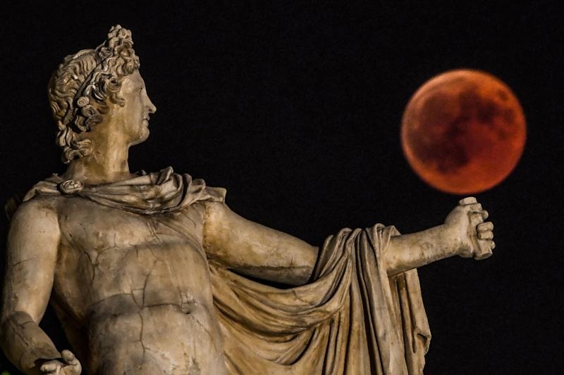 Rising beside a statue of the ancient Greek god Apollo in central Athens, Greece. (ARIS MESSINIS via Getty Images)