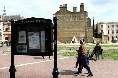 People walk past a sign on Windrush Square in the Brixton district of London, Britain April 16, 2018. REUTERS/Simon Dawson