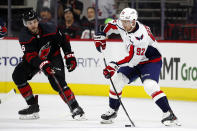 Washington Capitals' Evgeny Kuznetsov (92), of Russia, looks to pass the puck with Carolina Hurricanes' Joel Edmundson (6) nearby during the second period of an NHL hockey game in Raleigh, N.C., Friday, Jan. 3, 2020. (AP Photo/Karl B DeBlaker)
