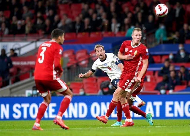 Harry Kane, centre, attempts a shot on goal against Hungary