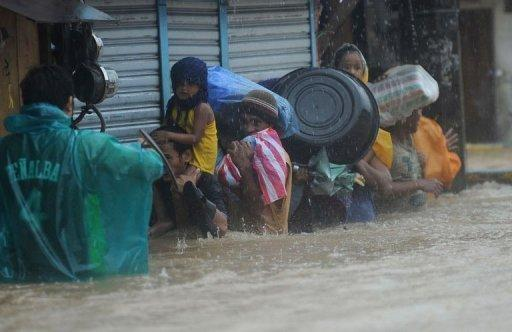 Residents wade through a flooded street under heavy rain as they are evacuated from their homes in the village of Tumana, Marikina town, in suburban Manila on August 7, 2012. Torrential rains have brought the Philippines capital to a standstill, forcing at least 20,000 people to flee their homes as floodwaters covered half the sprawling city, authorities said