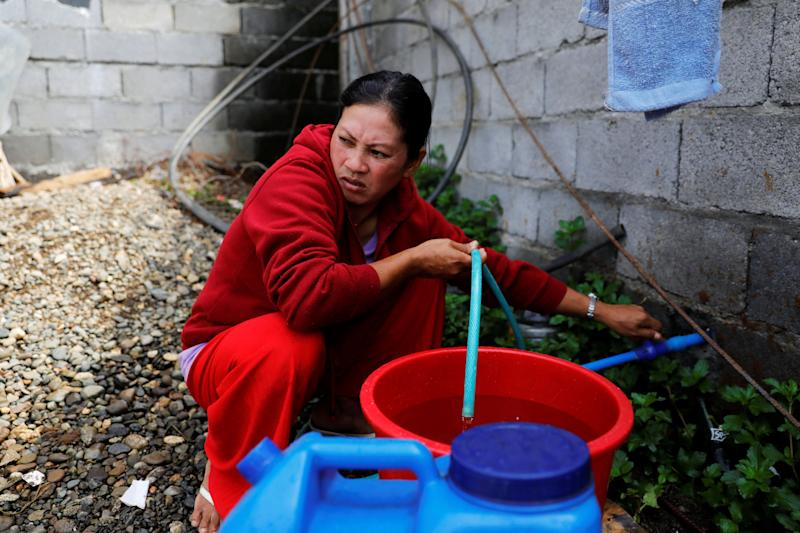 Marie Dalama Acampong, 37, fills containers with water at the only water source near the school-turned-evacuation center in Mipaga, Marawi City, Lanao del Sur province, Philippines. (Photo: Eloisa Lopez/Reuters)