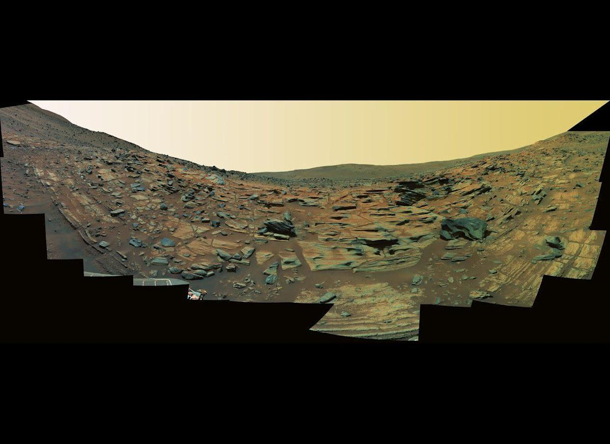 """This Spirit Pancam false-color panorama from mission sols 748-751 (February 9-12, 2006) shows what could be finely-layered lithified ash fall deposits along the edge of an ancient, worn-down volcanic cinder cone called Home Plate. <em>From """"Postcards from Mars"""" by Jim Bell; Photo credit: NASA/JPL/Cornell University</em>"""