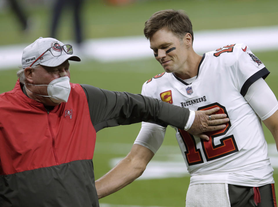 FILE - In this Jan. 17, 2021, file photo, Tampa Bay Buccaneers coach Bruce Arians, left, speaks with quarterback Tom Brady before the team's NFL divisional round playoff football game against the New Orleans Saints in New Orleans. Both Andy Reid and Arians are considered players coaches, though they do it in different ways. It's a quality thats helped them reach the Super Bowl. (AP Photo/Brett Duke, File)