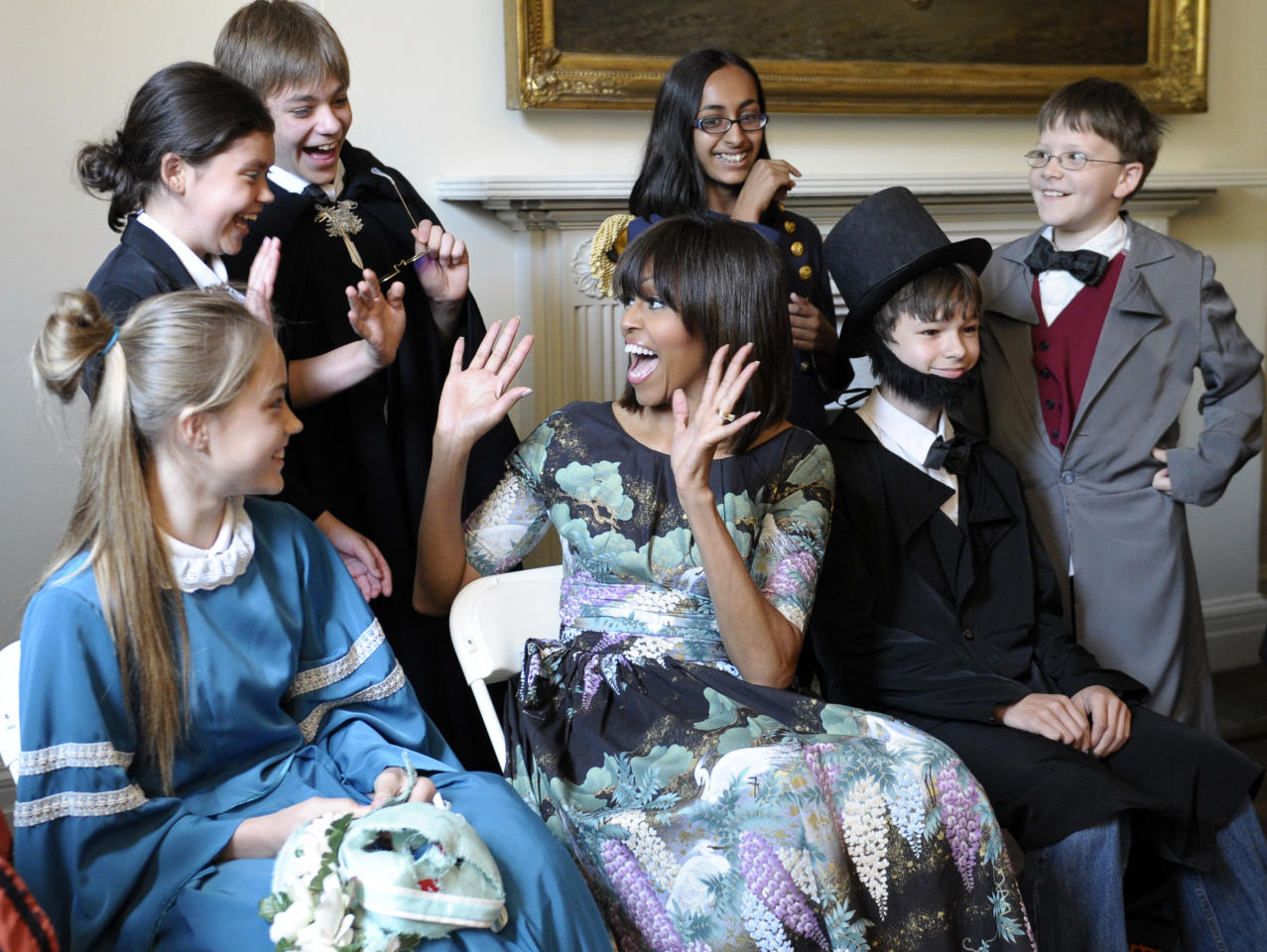 First lady Michelle Obama reacts as she surprises schoolchildren from Willow Springs Elementary School in Fairfax, Va., before they performed part of a play at the Decatur House, a National Trust for Historic Preservation Site and home to the David M. Rubenstein National Center for White House History, in Washington, Wednesday, May 22, 2013. The events were part of an announcement of a major philanthropic effort to preserve the Decatur House. (AP Photo/Susan Walsh)