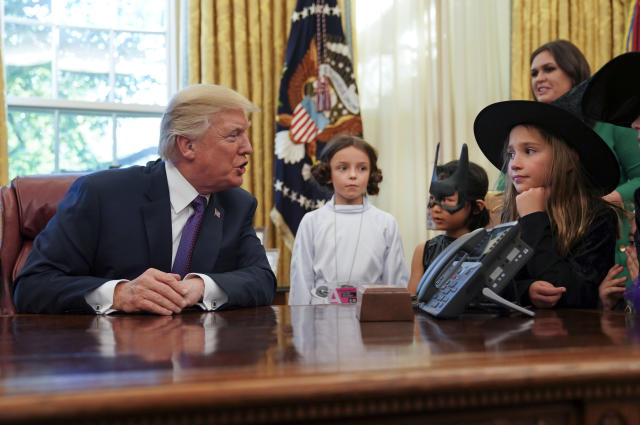President Donald Trump talks with from lwft, Natalynn Parkinson, 6, Yume Inone, 6, and Phoebe Trabb, 7, who are dressed in their halloween costumes, Friday, Oct. 27, 2017. (AP Photo/Pablo Martinez Monsivais)