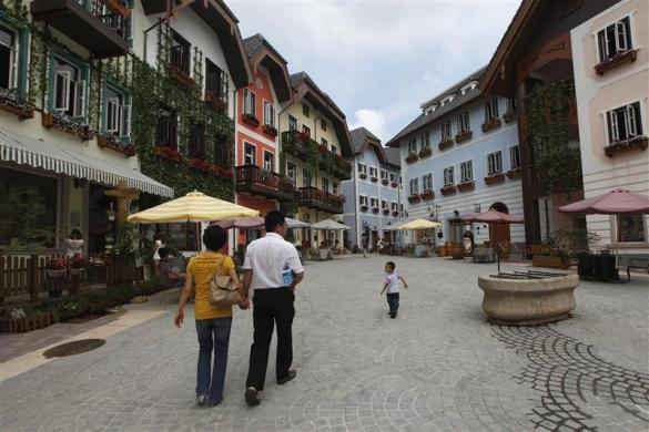 A family walks in the Chinese replica of Austria's UNESCO heritage site, Hallstatt village, in China's southern city of Huizhou in Guangdong province, June 1, 2012.