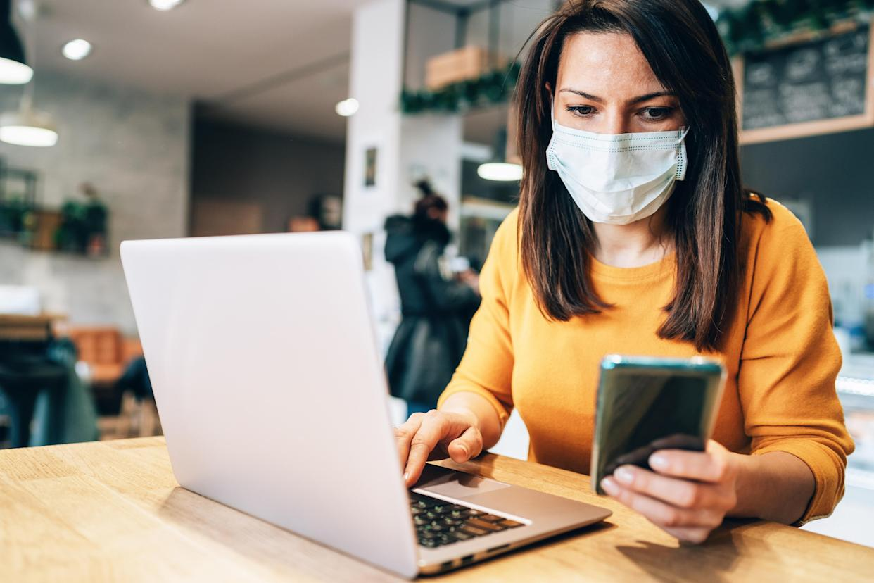 A woman uses a laptop at a cafe while wearing a face mask