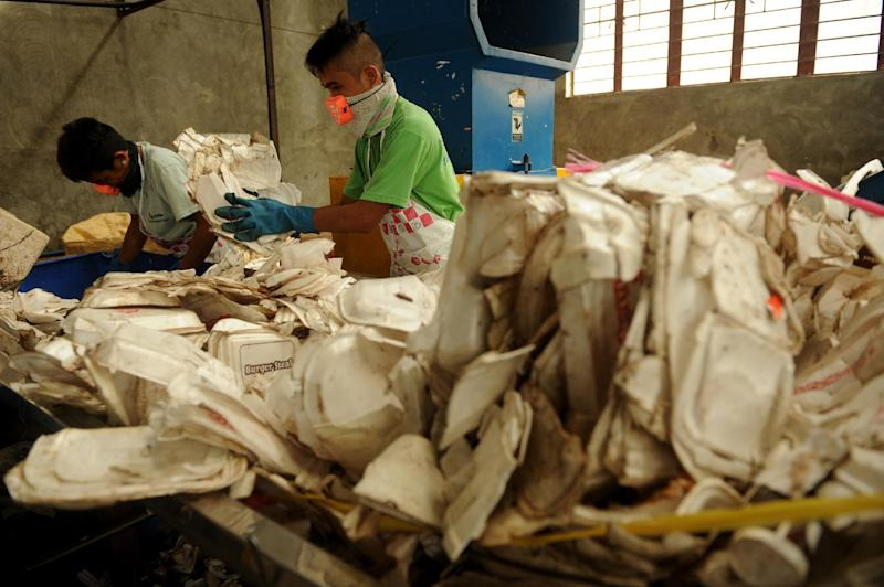 Employees place used styrofoam into a shredder at a recycling plant in Valenzuela City, north of Manila on June 11, 2013 (AFP Photo/Noel Celis)
