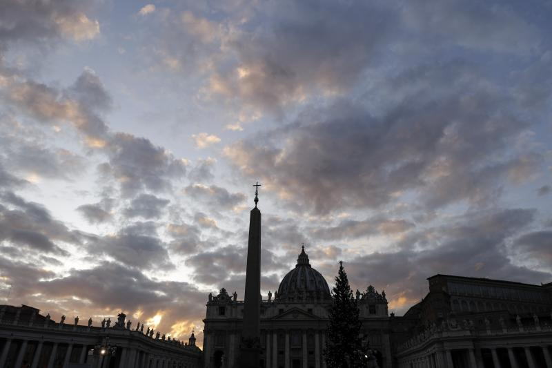 "FILE - In this Thursday, Dec. 5, 2019 file photo, the sun sets over St. Peter's Basilica, at the Vatican. Vatican prosecutors have ordered the seizure of documents and computers from the administrative offices of St. Peter's Basilica in an apparently new investigation into financial irregularities in the Holy See. The Vatican said Tuesday that Pope Francis has also named a special commissioner to run the basilica, reorganize its offices, update its statutes to comply with new Vatican norms on procurement contracts and to ""clarify its administration.""  (AP Photo/Gregorio Borgia, File)"