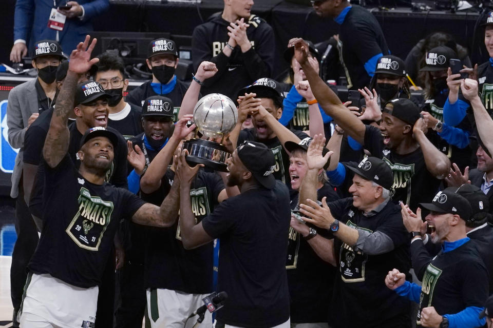 The Milwaukee Bucks celebrate with the conference trophy after defeating the Atlanta Hawks in Game 6 of the Eastern Conference finals in the NBA basketball playoffs, Saturday, July 3, 2021, in Atlanta. (AP Photo/John Bazemore)