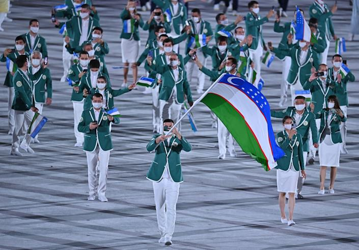 <p>Uzbekistan's flag bearer Bakhodir Jarolov leads the delegation during the opening ceremony of the Tokyo 2020 Olympic Games, at the Olympic Stadium, in Tokyo, on July 23, 2021. (Photo by Ben STANSALL / AFP) (Photo by BEN STANSALL/AFP via Getty Images)</p>