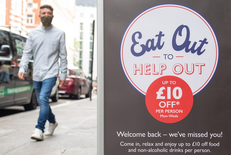 File photo dated 3/8/2020 of a man passing a sign advertising the 'Eat Out to Help Out' scheme. Three men have been arrested on suspicion of fraud relating to the Eat Out to Help Out discount scheme, HM Revenue and Customs (HMRC) has said.