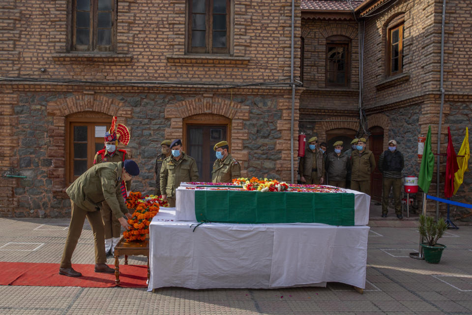 An Indian police officer lays a wreath as he pays respect to colleagues killed in an attack in Srinagar, Indian controlled Kashmir, Friday, Feb. 19, 2021. Anti-India rebels in Indian-controlled Kashmir killed two police officers in an attack Friday in the disputed region's main city, officials said. Elsewhere in the Himalayan region, three suspected rebels and a policeman were killed in two gunbattles. (AP Photo/ Dar Yasin)